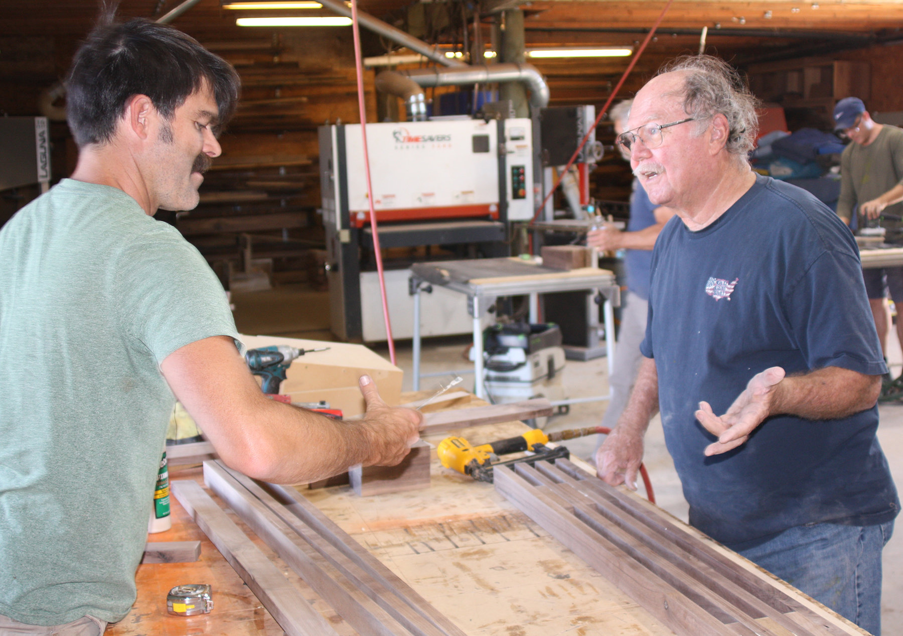 Jory Brigham assists Bruce Kuveke as he assembles the slats for his custom wood and metal bench.