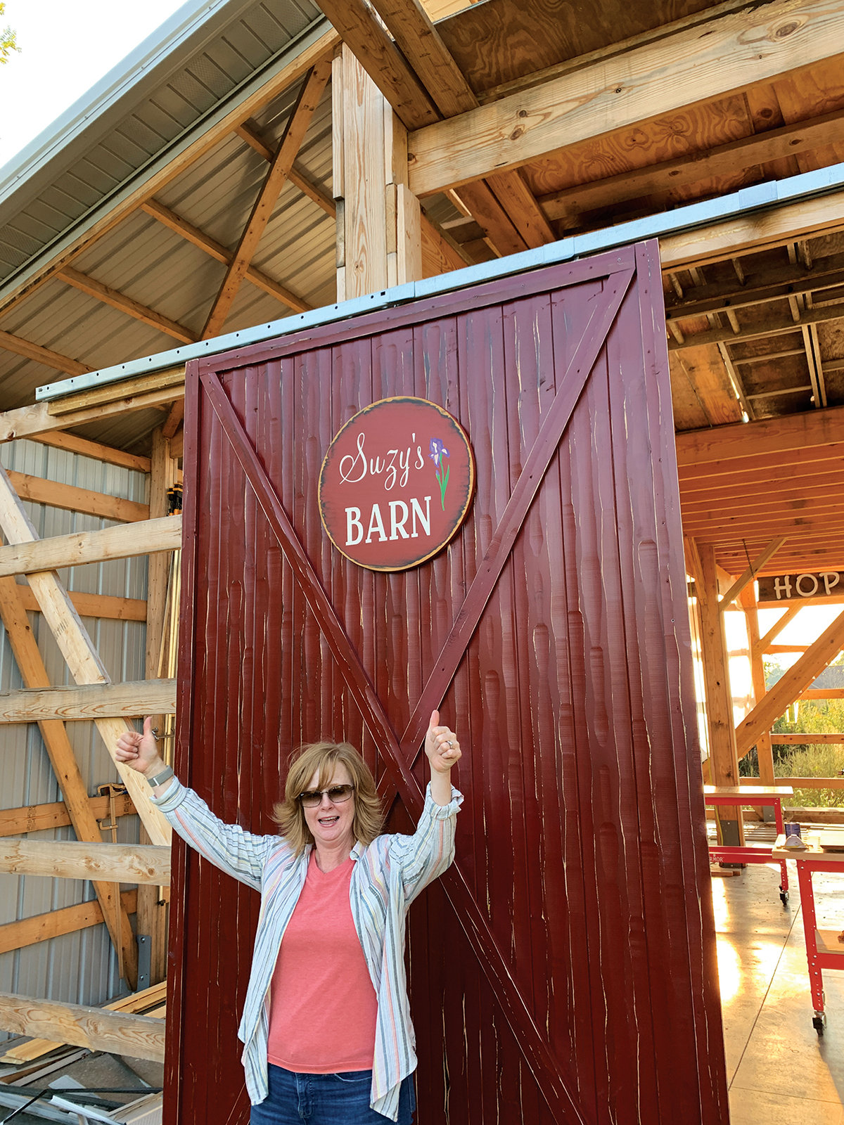 Suzy celebrates a finished barn door complete with sign.